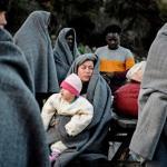 Des migrants arrivés à Lesbos depuis la Turquie jeudi tentent de se réchauffer après avoir passé la nuit dehors sous la pluie. Ils font sécher tant bien que mal leurs vêtements. Image: AFP