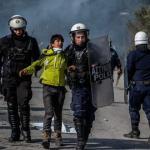 Un jeune migrant emporté par la police après des heurts survenus près du camp de réfugiés à Lesbos en Grèce le 2 mars.