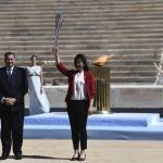 La nageuse Imoto Naoko reçoit la flamme olympique des mains du président du Comité olympique grec, Spyros Capralos, ce jeudi.