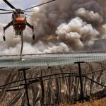 Un hélicoptère pompe de l'eau dans un réservoir à proximité de Corinthe pour lutter contre l'un des nombreux incendies qui touchent la Grèce cet été. VASSILIS PSOMAS / REUTERS