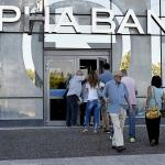 Les banques grecques ont réouvert le 20 juillet dernier, mais les retraits restent plafonnés, ce qui encourage les Grecs à se tourner vers le paiement par carte - AFP PHOTO / ARIS MESSINIS