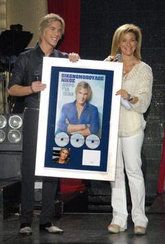 Avec le directeur de Minos-EMI, Margarita Matsa, lors de la cérémonie de remise du triple disque de platine pour « Doro gia sena », en mai 2011. (photo Manolis Chiotis)