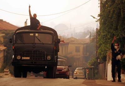 En guerre contre le feu. Des soldats évacuent un village en feu près de l'Olympie