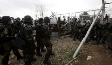 Des migrants tentent de forcer la barrière qui sépare la Grèce de la Macédoine, le 29février.