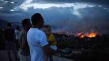 Des Grècs observent un feu de forêt à Rafina dans la banlieue d'Athènes, en Grèce