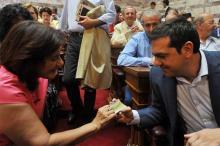 La ministre déléguée à la Solidarité sociale, Theno Photiou, montre la nouvelle Carte de Solidarité au premier ministre Alexis Tsipras.